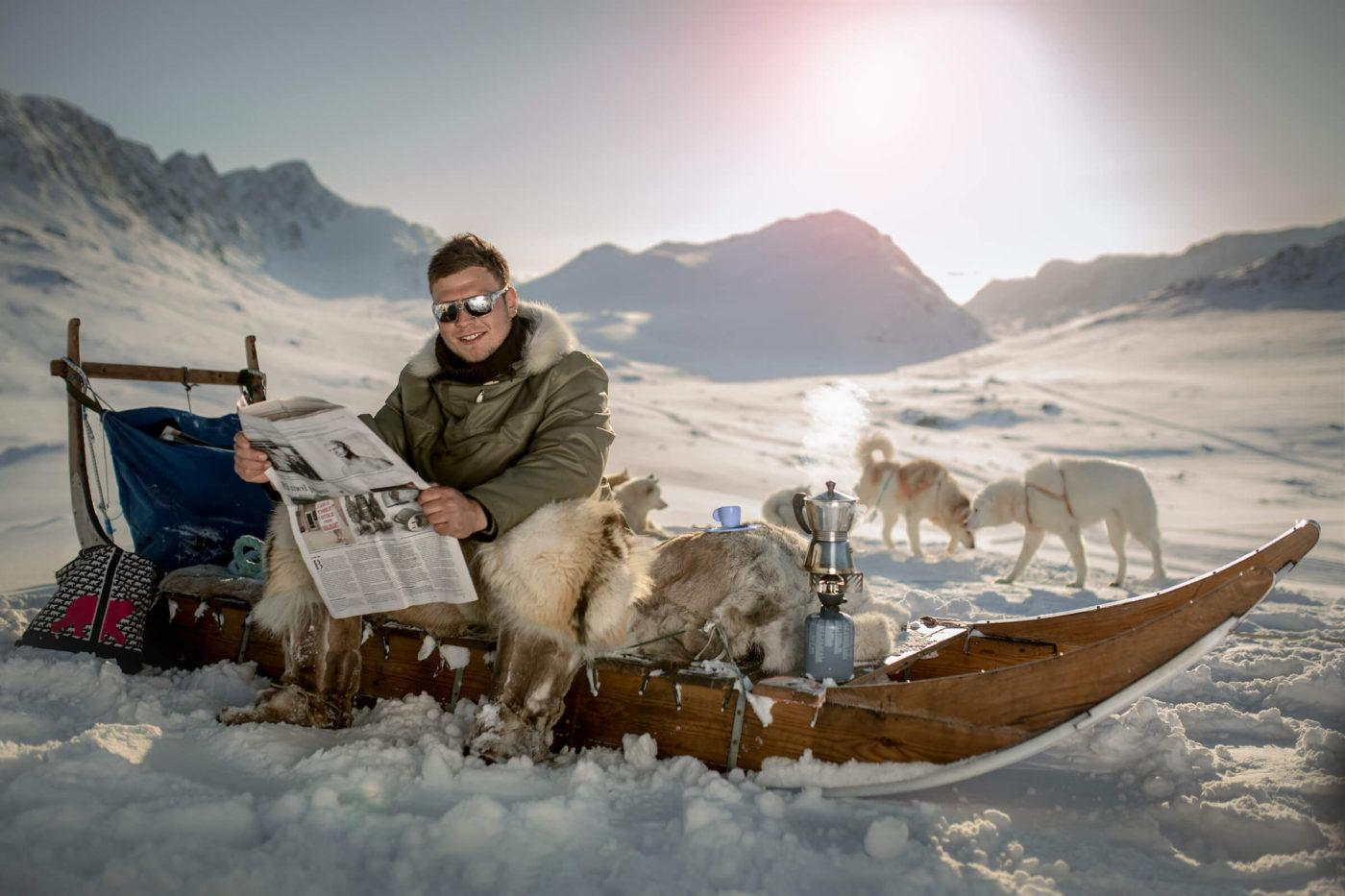 Dog sled driver from Sisimiut brewing espresso and reading a newspaper
