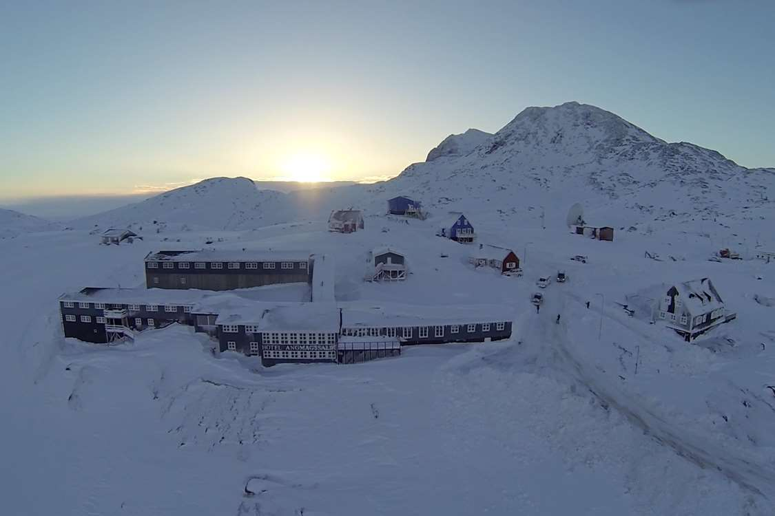 Aerial view of the hotel with sunrise in background in Winter. Photo by Hotel Angmagssalik - Visit Greenland