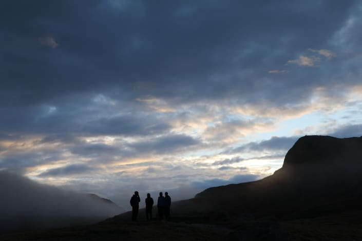Hikers on mountain top with fog, sun and clouds. Photo by Morten Christensen