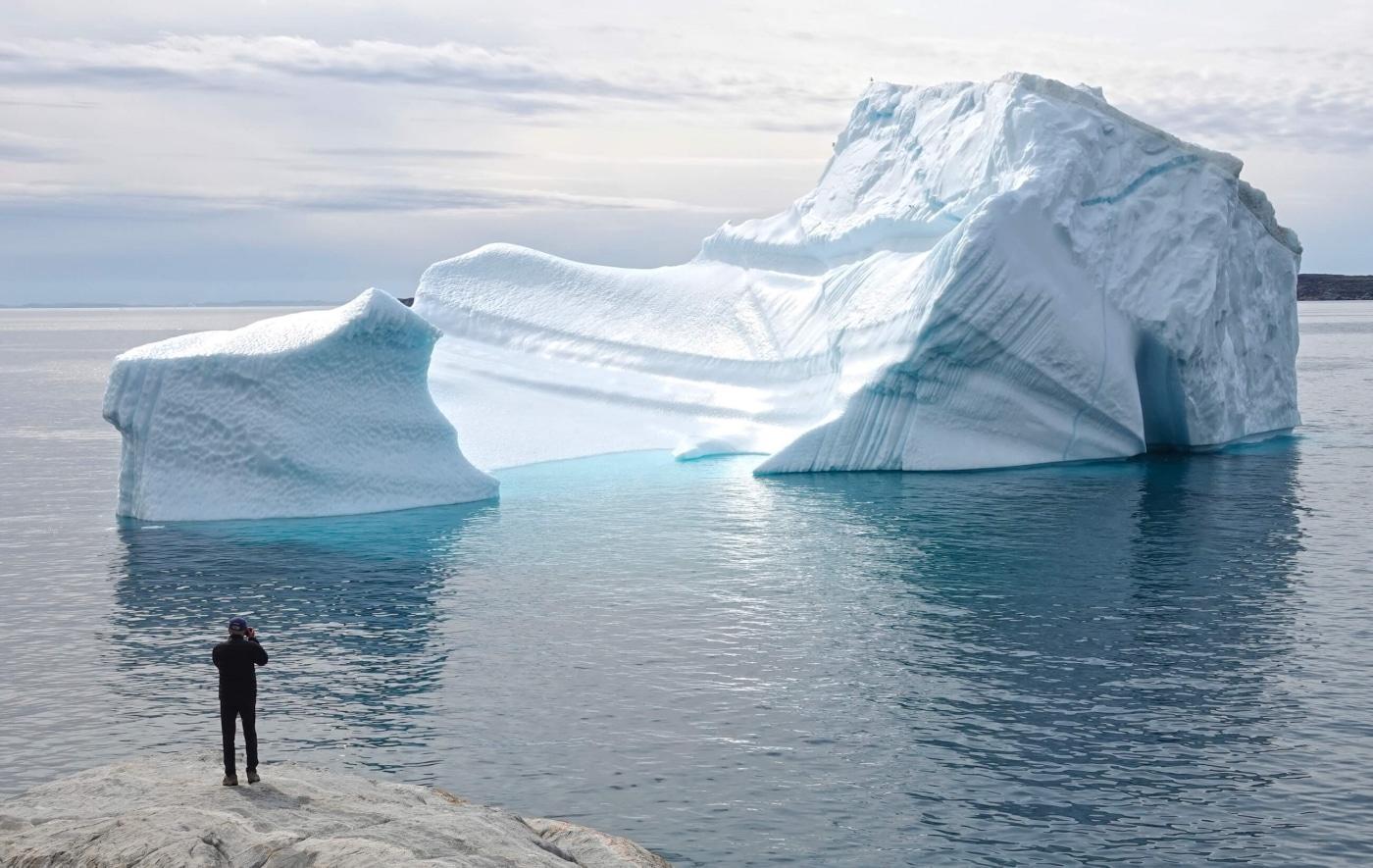 Man looking at a large iceberg near Disko Bay. Photo by Espen Andersen, Visit Greenland