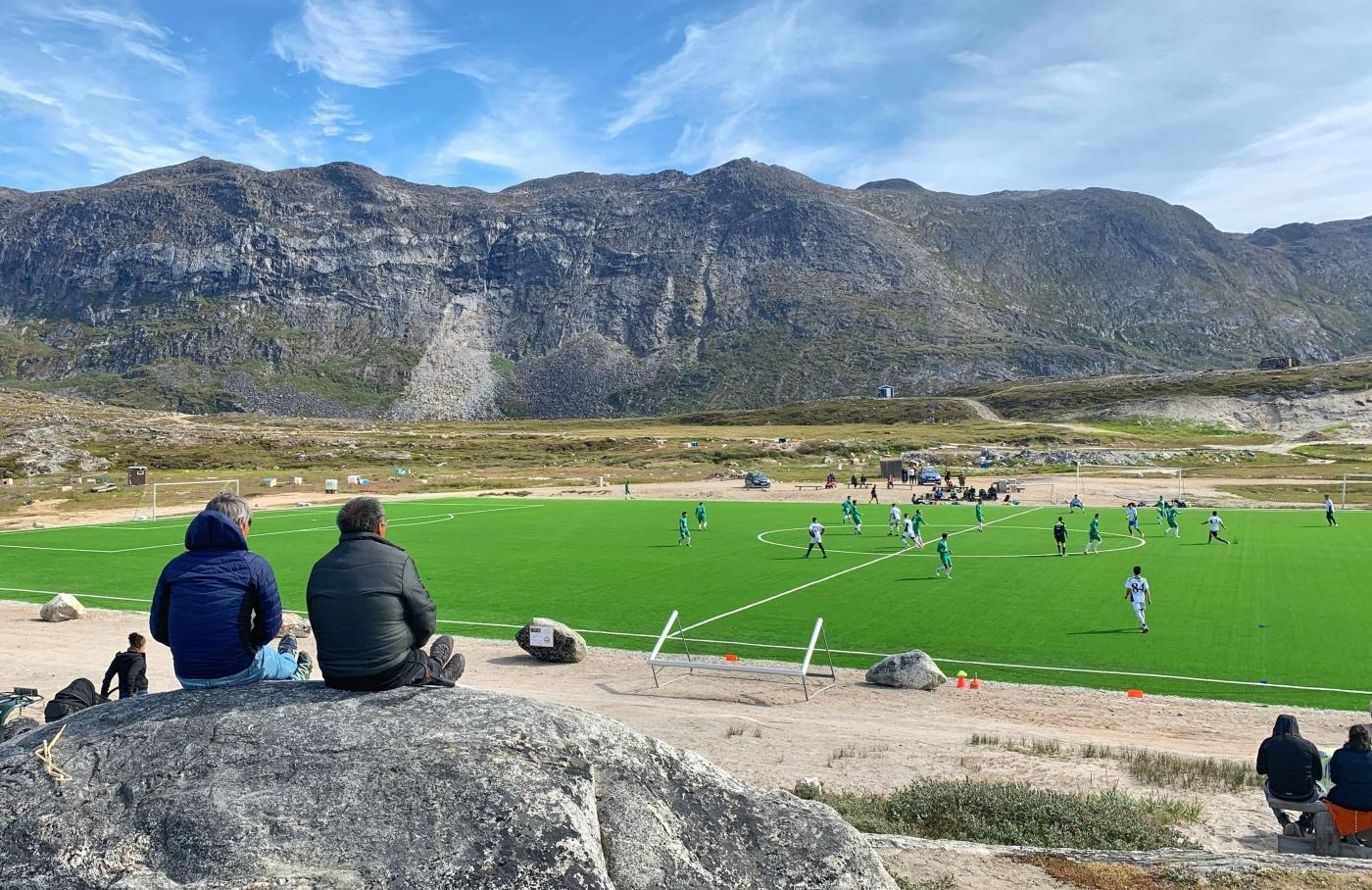 Two people sitting on a rock watching a soccer game. Photo by Espen Andersen, Visit Greenland