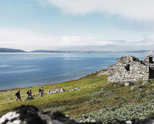 Hikers approaching Hvalsey church ruin one of several norse historical sites in south greenland. By David Trood