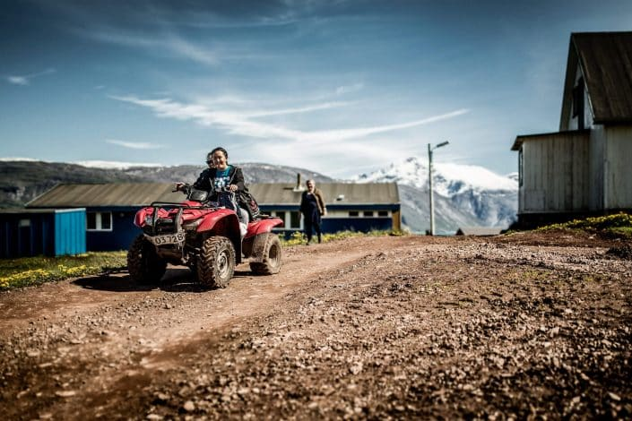 Two girls driving an ATV through Qassiarsuk in South Greenland. Photo by Mads Pihl.