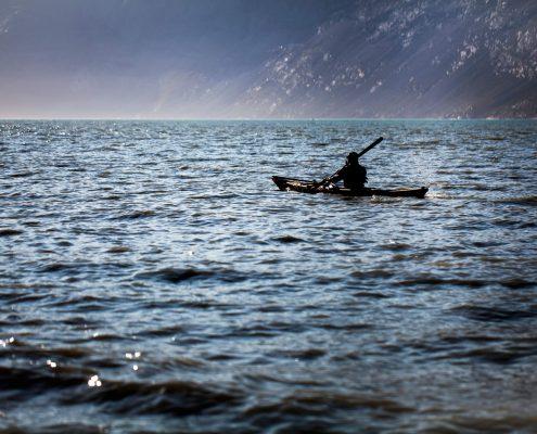 Kayaker near mountainside. By Mads Pihl