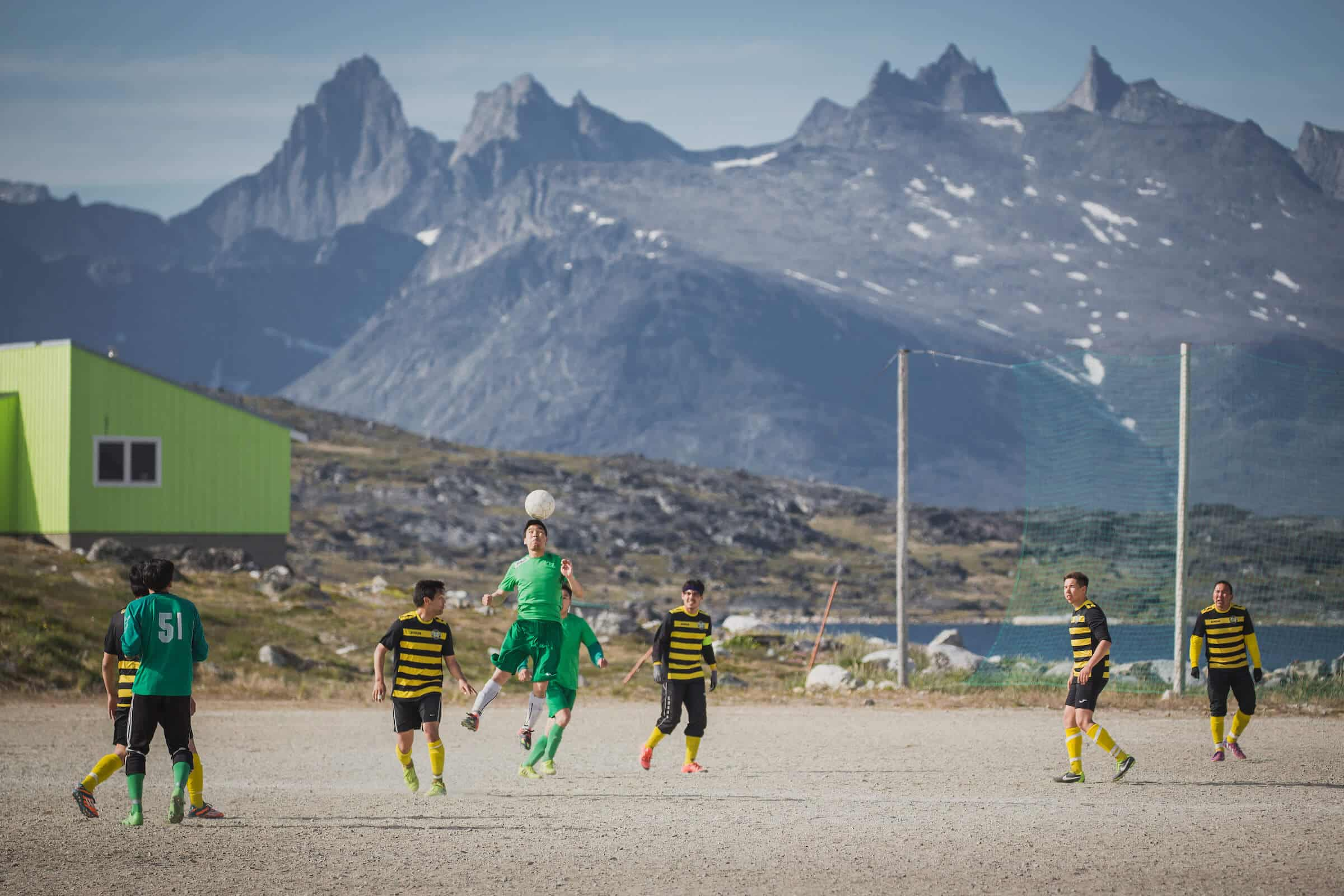 A game of soccer in Nanortalik in South Greenland with a backdrop of rugged peaks. Photo by Mads Pihl.