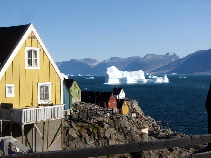 A typical view in Uummannaq with houses on rocky cliffs and icebergs in the background in North Greenland. By Ella Grødem