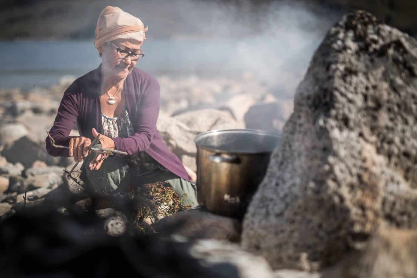 A woman preparing food over open fire in Narsaq in South Greenland. Photo by Mads Pihl.