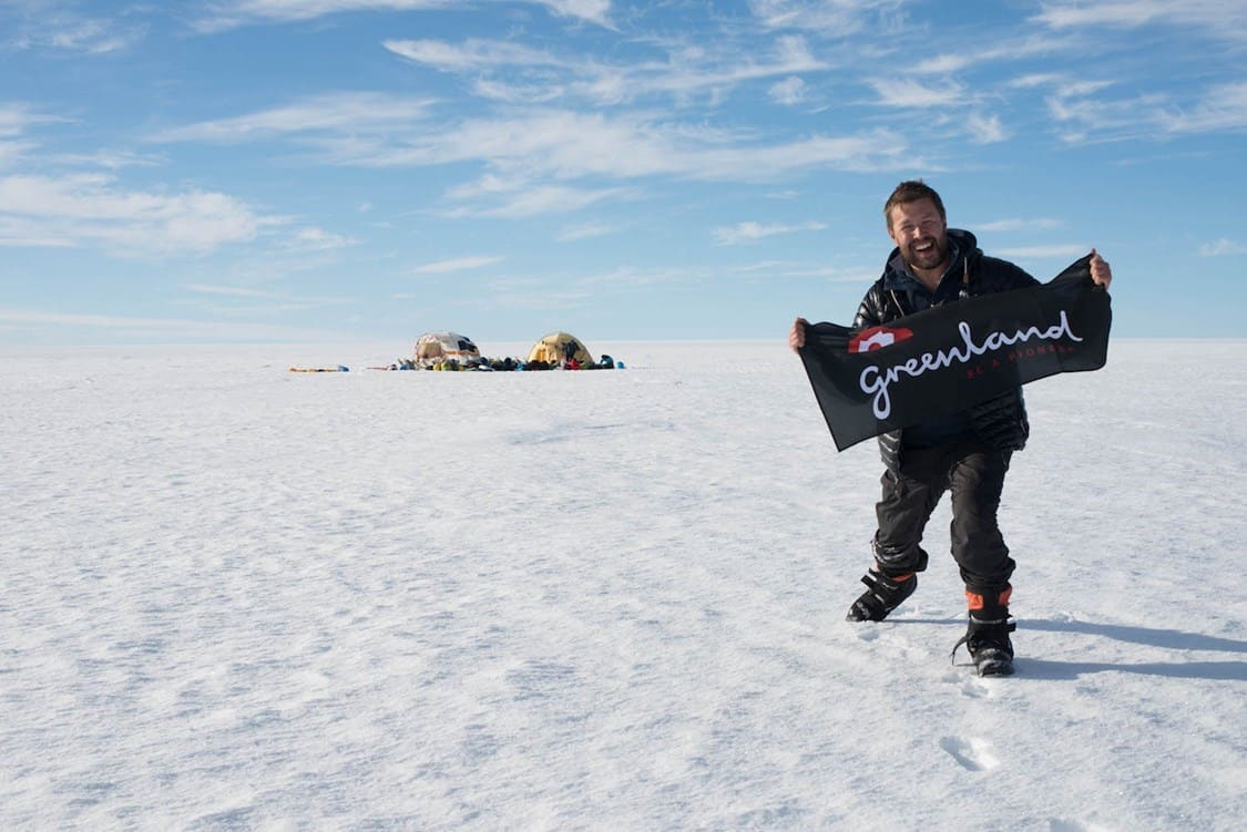 """The author on the East Greenland section of the inland ice with a """"Greenland, Be a Pioneer"""" flag. By Malik Milfeldt"""