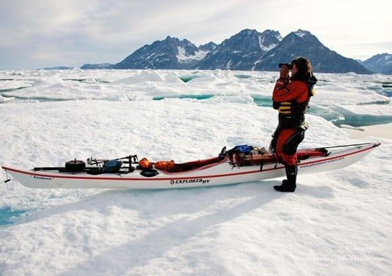 Kayaker overlooking the landscape of ice and mountains. By N. A. Antognelli