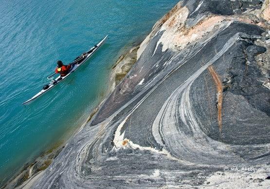 Kayaker near rock formation. By N. A. Antognelli