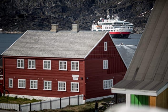 MS Fram behind old building in Qeqertarsauq in Greenland. Photo by Mads Pihl.