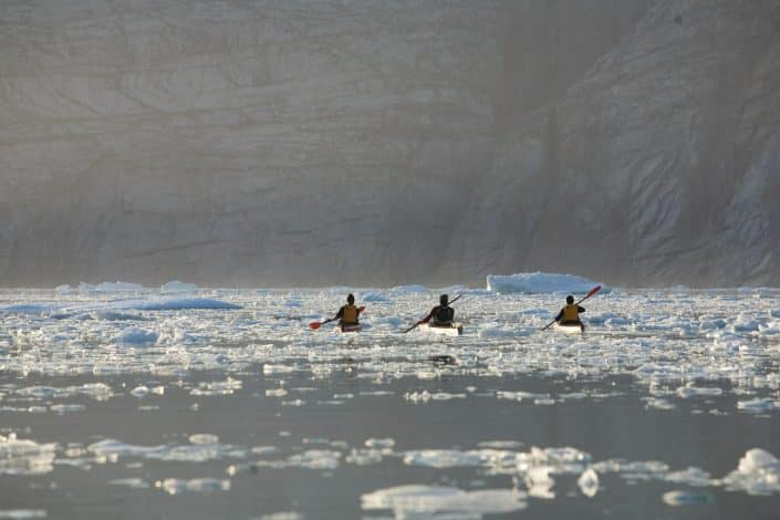 Three kayakers navigating through ice-cakes. Photo by Glenn Mattsing.