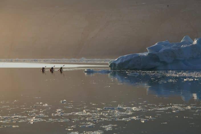 Three kayakers next to iceberg in midnight sun. Photo by Glenn Mattsing.