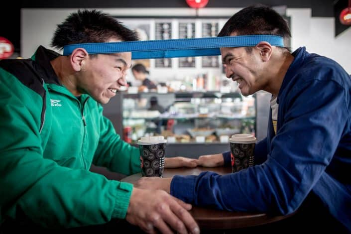 Two Inuit games athletes practicing the head pull before the Arctic Winter Games at a cafe in Nuuk in Greenland. By Mads Pihl