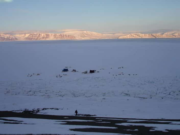 Man walking in backcountry of Qaanaaq towards hunting camp on ice in Winter. Photo by Nunataq Atsuk Travel