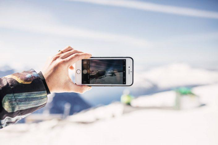 Female hand holding a smartphone while taking picture with smartphone at the top of Qingaaq mountain in Nuuk fjord. Photo by Filip Gielda