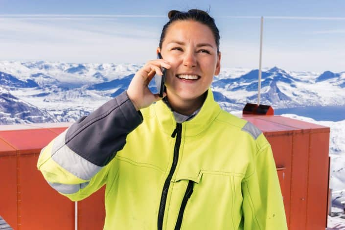 Portrait of Tele-Post employee - Nina Høegh Møller talking by the phone at the top of Qingaaq moutain in Nuuk fjord. Photo by Filip Gielda