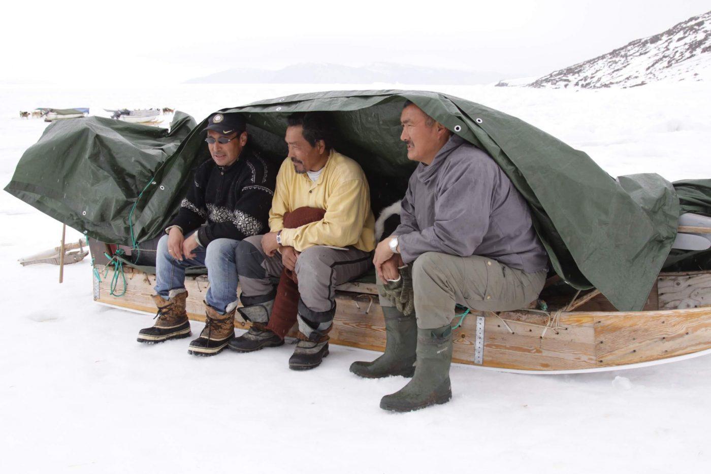 Three local men sitting on a sleigh under a tarpaulin in Qaanaaq, North Greenland. Photo by Nunataq Atsuk Travel