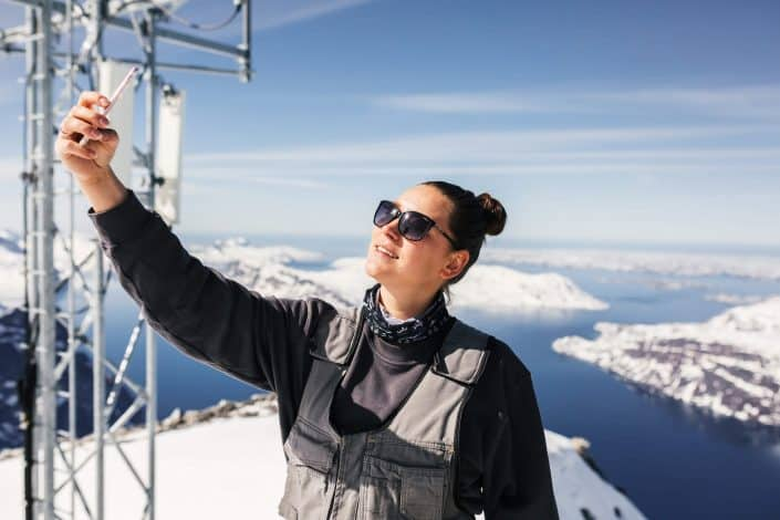 Tele-Post's employee takes a selfie picture at the top of Qingaaq mountain in Nuuk fjord. Photo by Filip Gielda