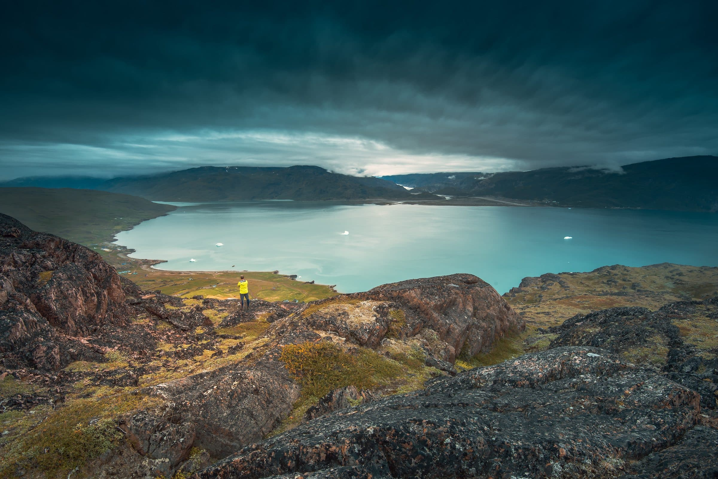 A lone traveller stands in Qassiarsuk and looks over Tunulliarfik Fjord toward Narsarsuaq. Photo by Stacy William Head