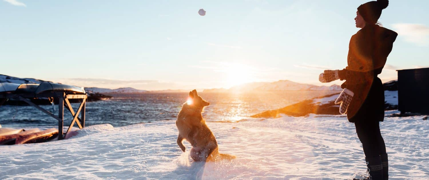 Local make up artist Natascha playing with her dog in the snow during sunset in Nuuk in Greenland. Photo by Rebecca Gustafsson