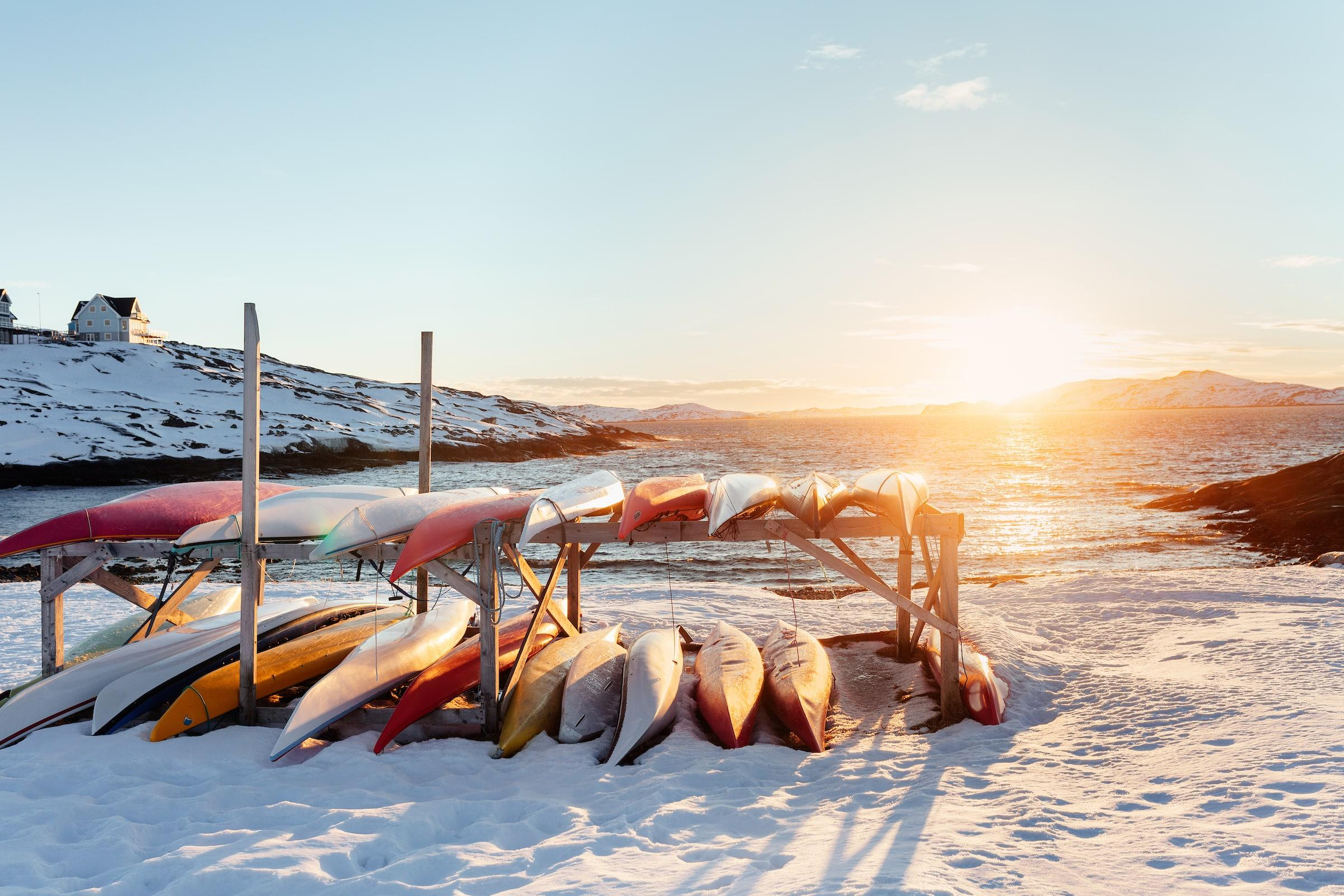 Backlit kayaks in a sunset scene in Nuuk in Greenland. Photo by Rebecca Gustafsson - Visit Greenland.