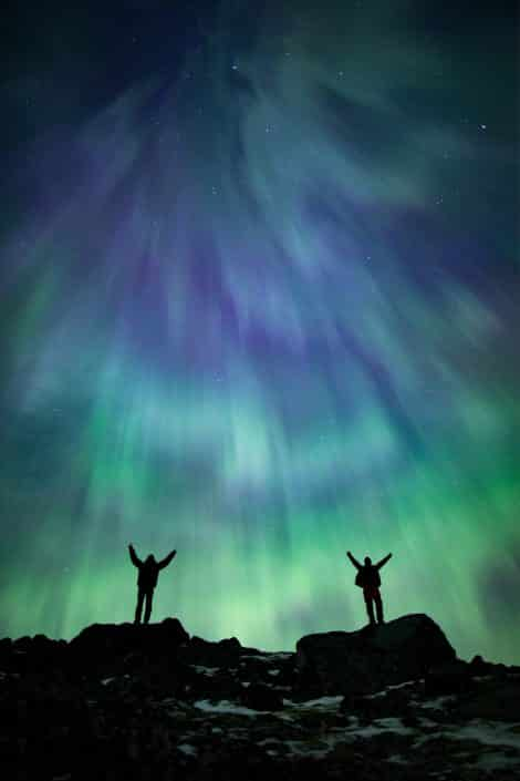Two travellers celebrate being on the trip of their lifetime underneath late summer Northern Lights in South Greenland. Photo by Paul Zizka – Visit Greenland