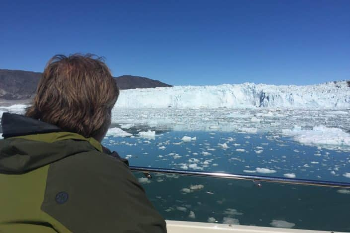 Tourist looking over a glacier from a boat under clear blue skies. Photo by Arctic Nomad