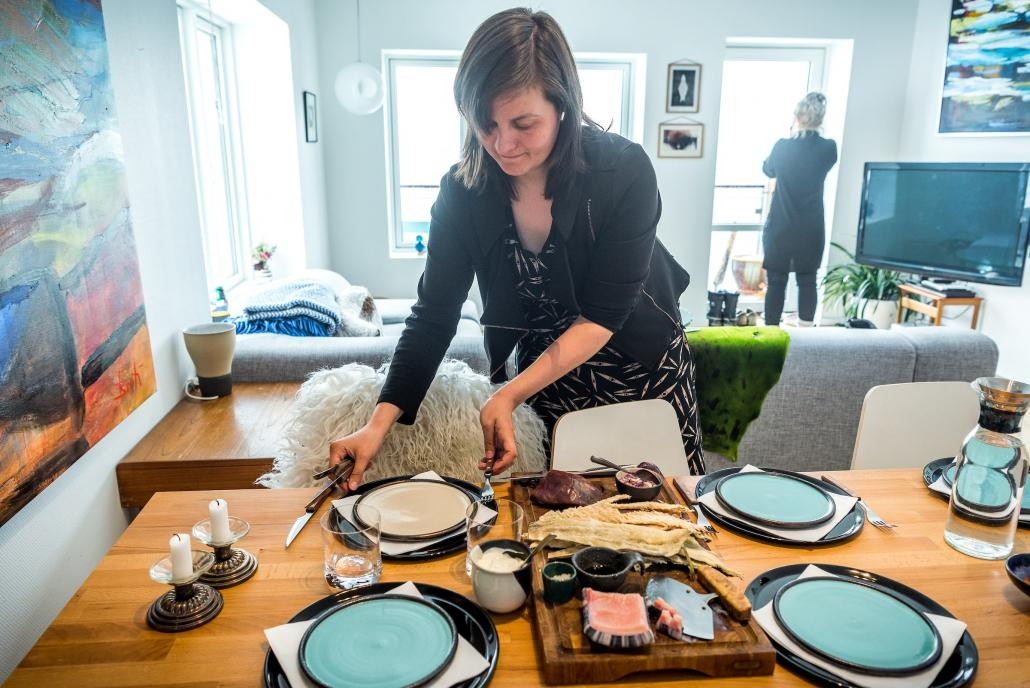Nivi Christensen, Director of Nuuk Art Museum sets table with traditional food. Photo – Lola A. Åkerström, Visit Greenland