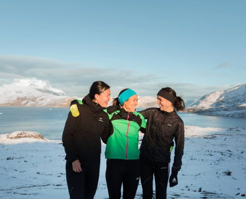 Three friends posing for a photo in running clothes in Nuuk in Greenland. Photo by Rebecca Gustafsson - Visit Greenland