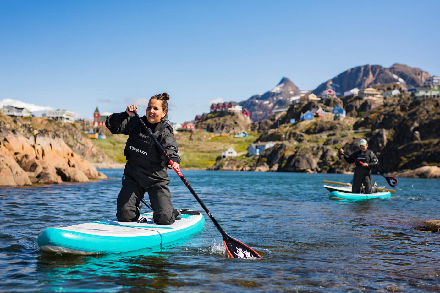 Two SUP with Sisimiut in the back. Photo by Aningaaq R Carsen, Visit Greenland