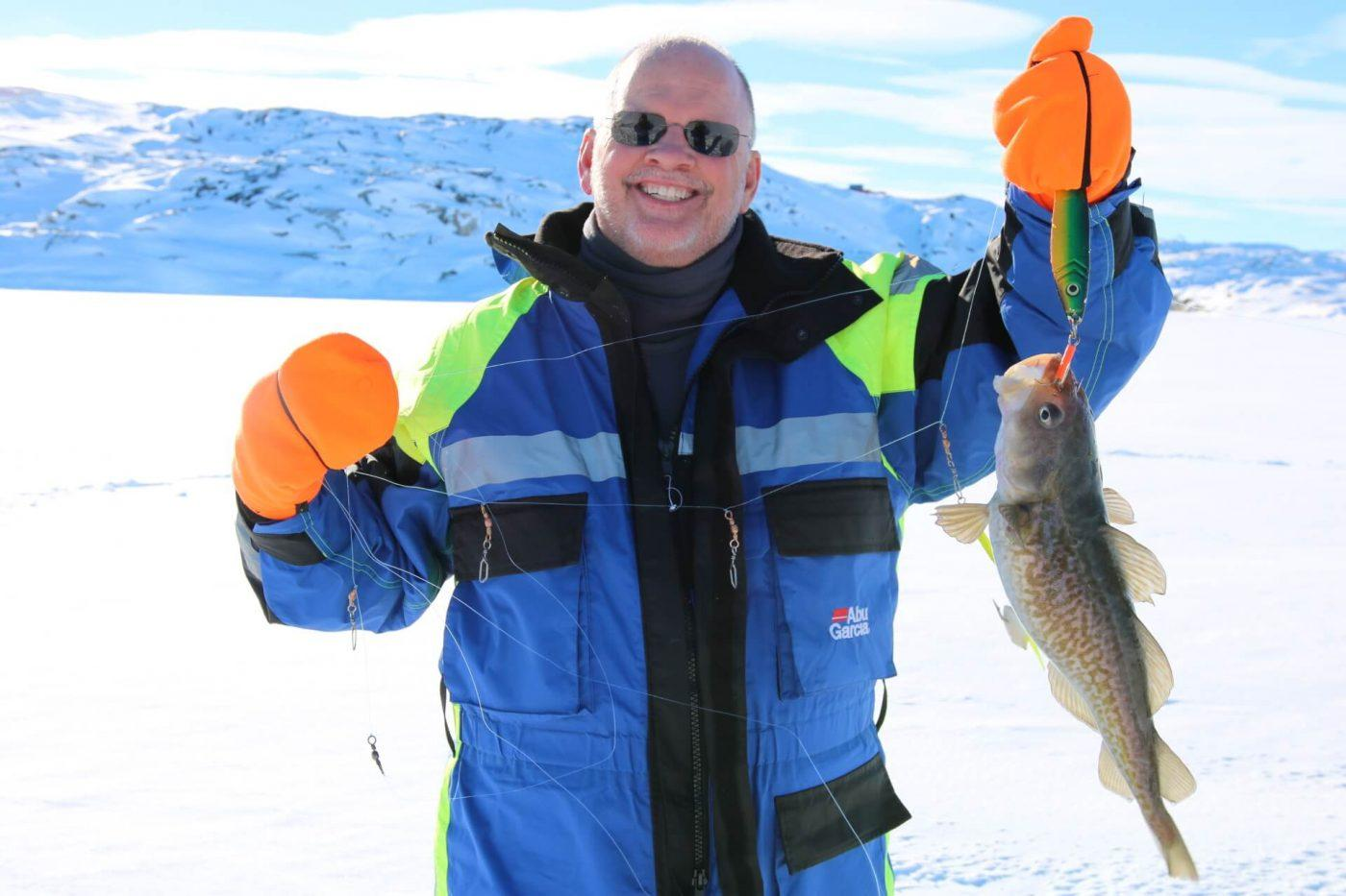 Happy tourist with his catch from ice fishing. Photo by Ilulissat Water Safari