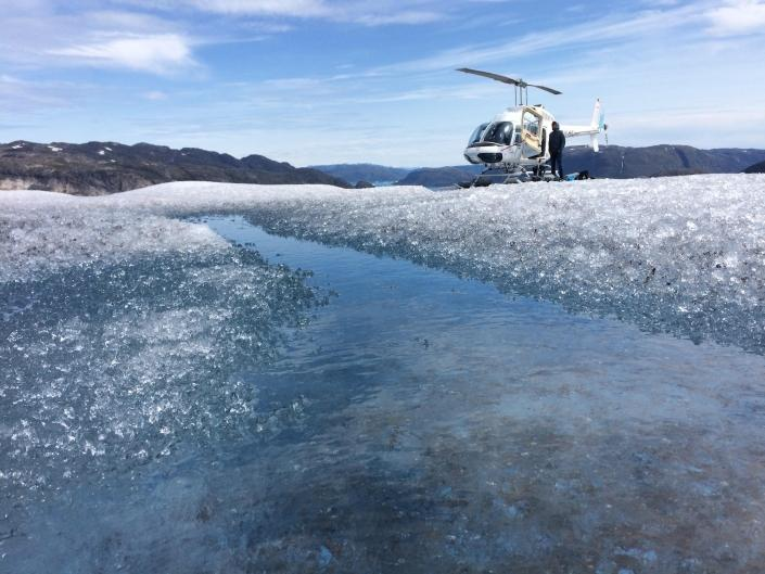Sermeq Helicopters on ice with pilot standing beside the helicopter in Summer. Photo by Pilu Nielsen, Visit Greenland.