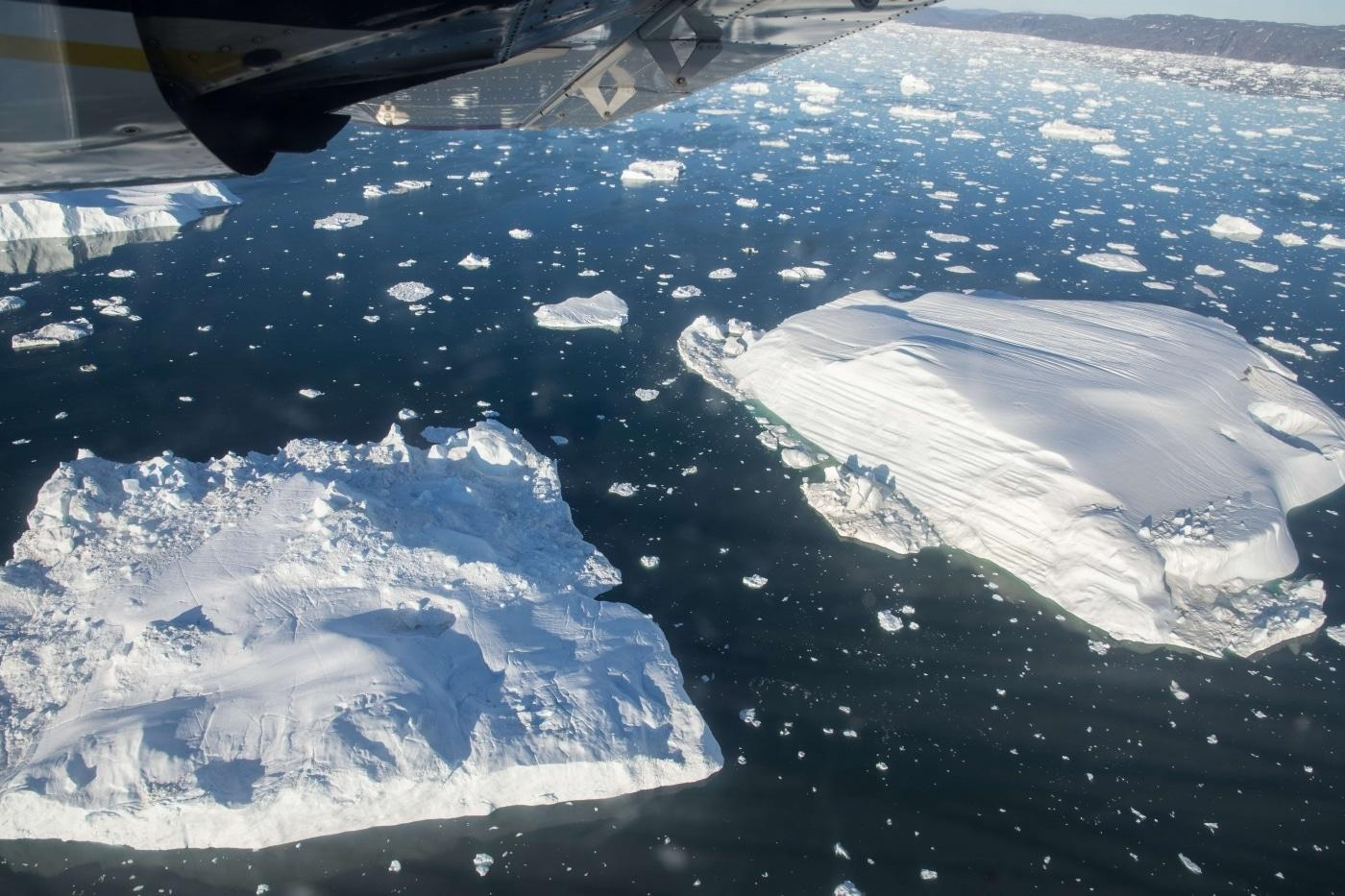 View from flight looking down at icebergs in the arctic ocean. Photo by Guide to Greenland