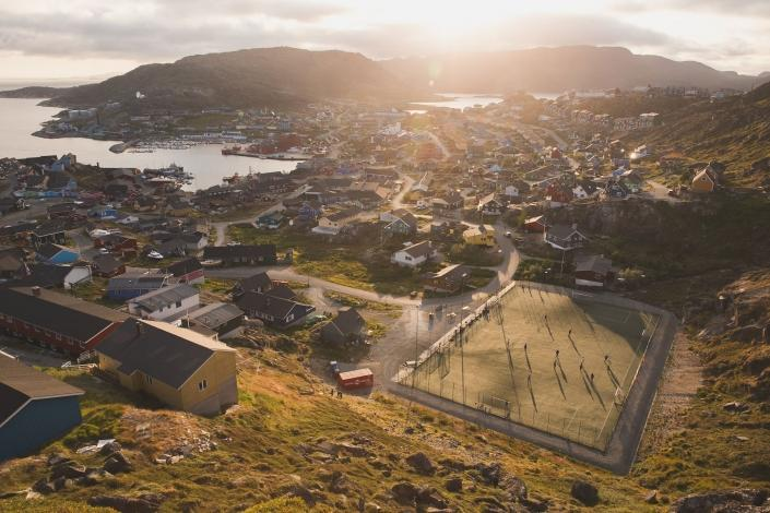 Sunset over a game of soccer and Qaqortoq in South Greenland. Photo by Mads Pihl