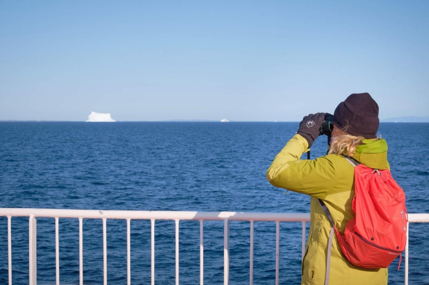 Passenger looking for whales through binoculars as Sarfaq Ittuk sails through Disko Bay - iceberg in the distance. Photo by Lisa Germany