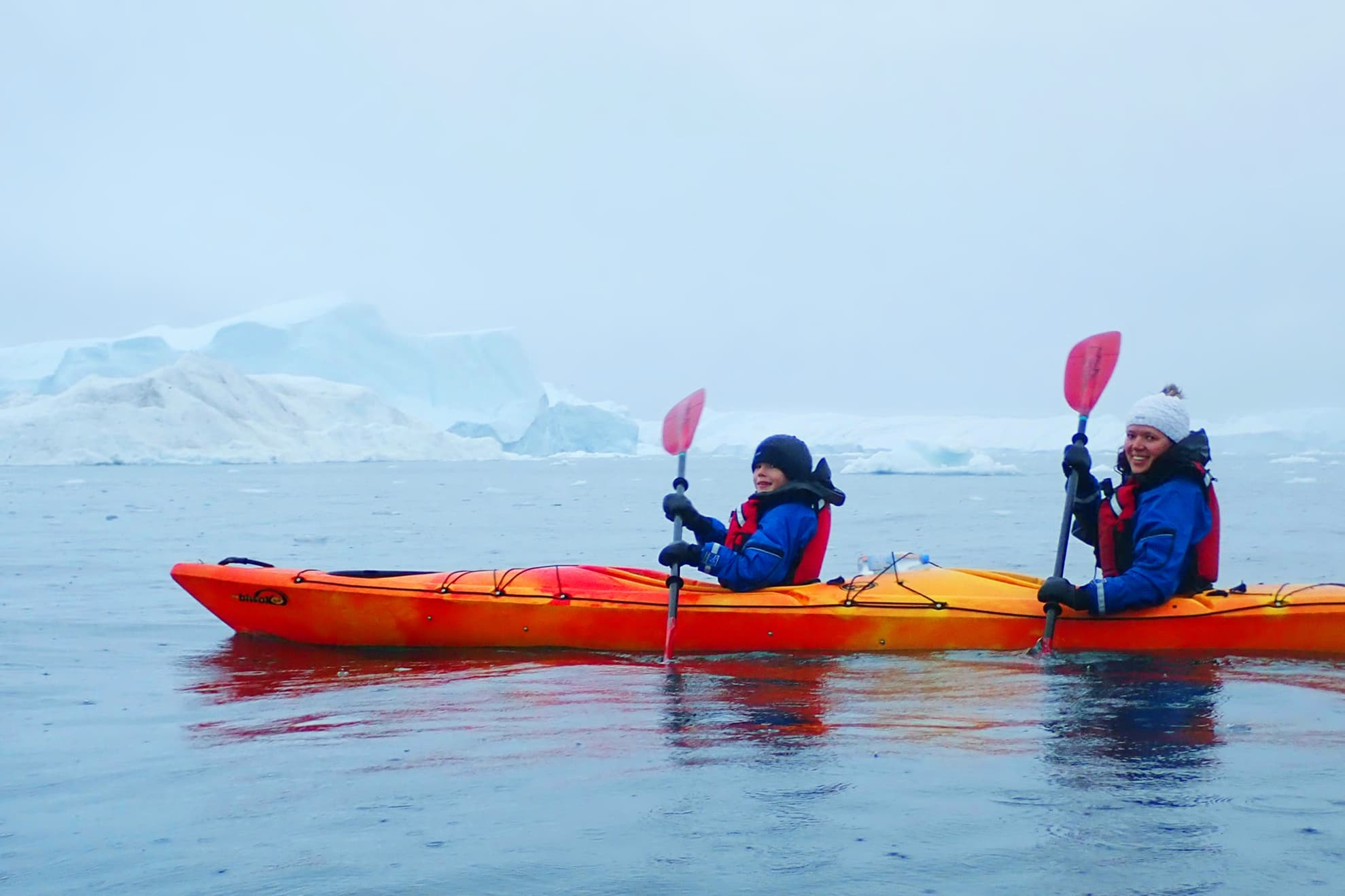 Family kayaking between icebergs in Greenland. Jurga Rubinovaite.