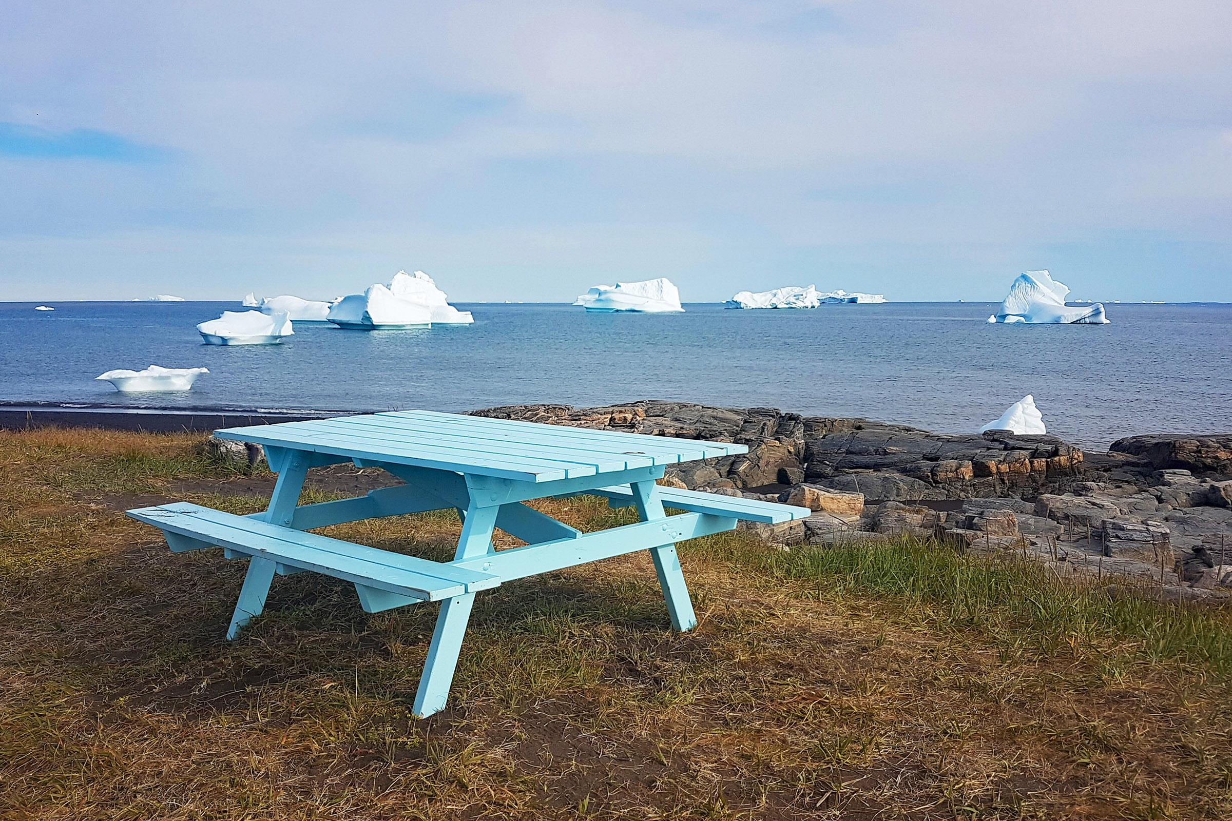 Picnic table with icebergs in the background in Qeqertarsuaq on Disko Island in Greenland. Jurga Rubinovaite.