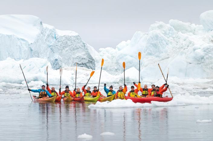 Kajakgruppe med pagajer i luften foran isbjerg. Photo by David D. Grant