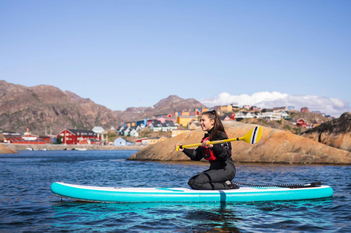 SUP near Sisimiut kneeling on her board. Photo - Aningaaq R. Carlsen, Visit Greenland
