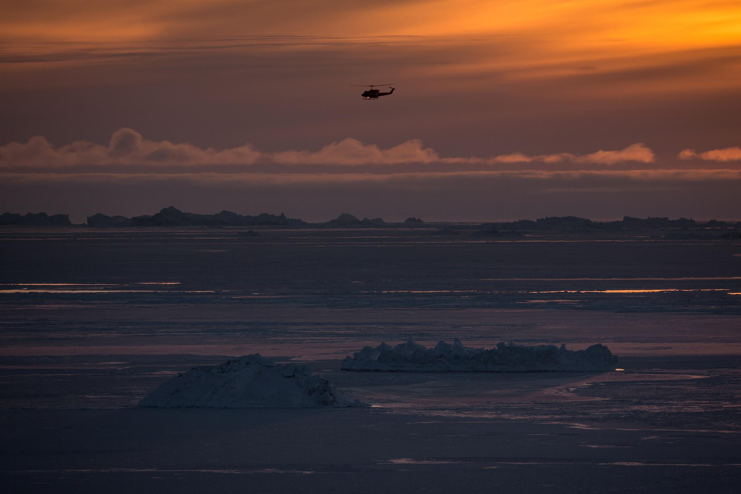 A Bell 212 Air Greenland helicopter over the Disko Bay in the sunset. Photo by Mads Pihl