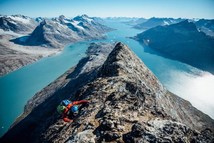 A climber scrambles a summit ridge, looking South down two fjords, West Of Tasiilaq Fjord. By Chris Brinlee Jr