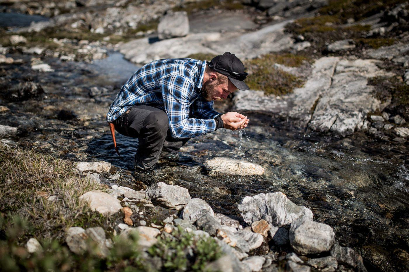 A hiker in East Greenland drinking pure, fresh water from a stream. Photo by Mads Pihl