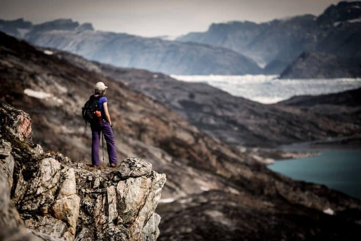 A hiker looking out towards Sermilik Ice Fjord north of Tiniteqilaaq in East Greenland. By Mads Pihl