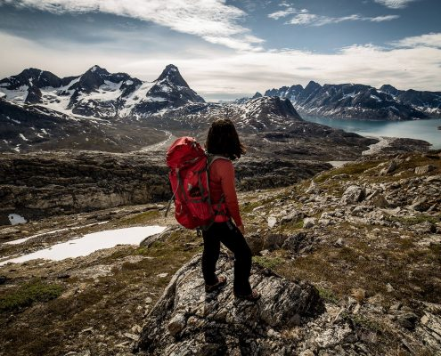 A hiker looking towards Tasiilaq Island in East Greenland
