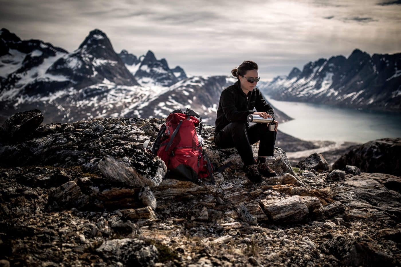 A hiker pouring coffee high in the hills above Tiniteqilaaq in East Greenland. By Mads Pihl