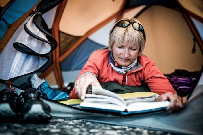 A hiker reading a book in a tent in East Greenland. By Mads Pihl