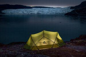 A lamp lit tent near the Eqi Glacier at dusk in Greenland. Photo by Mads Pihl