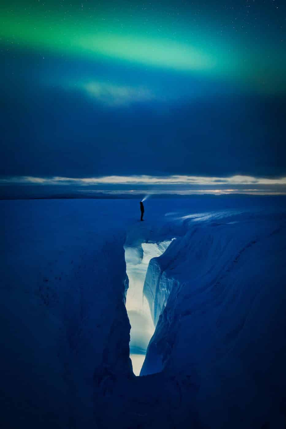 A man with a flash light looking up to the northern lights by a crevasse on the Greeland Ice Sheet near Kangerlussuaq. By Paul Zizka