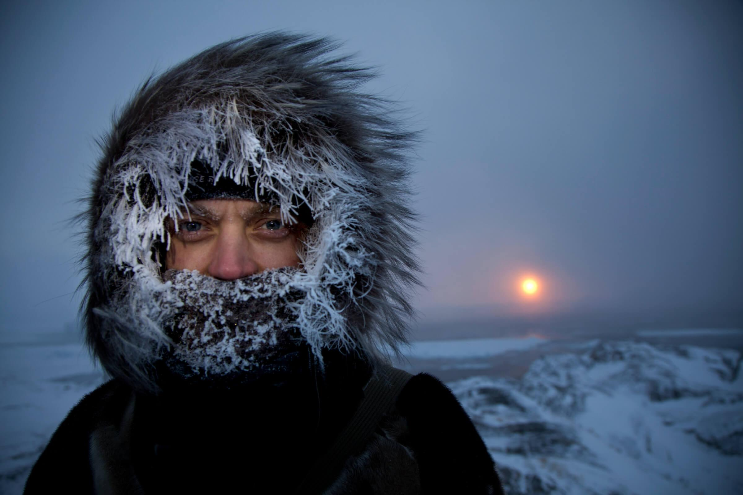 A midwinter portrait near the Ilulissat Ice Fjord in Greenland with the sun setting in the background